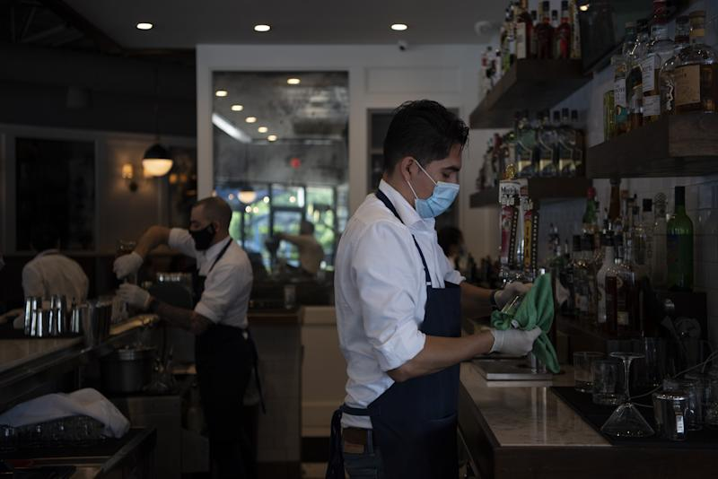 Employees wear protective masks and gloves at a restaurant in Houston, Texas, as the state reopens. Source: Getty