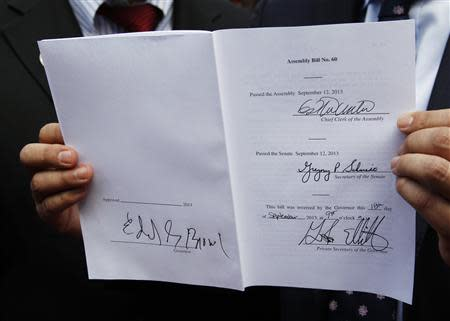 """A copy of the """"AB60"""" that California Governor Jerry Brown (unseen) signed into law is seen after ceremonies in Los Angeles October 3, 2013. REUTERS/Fred Prouser"""