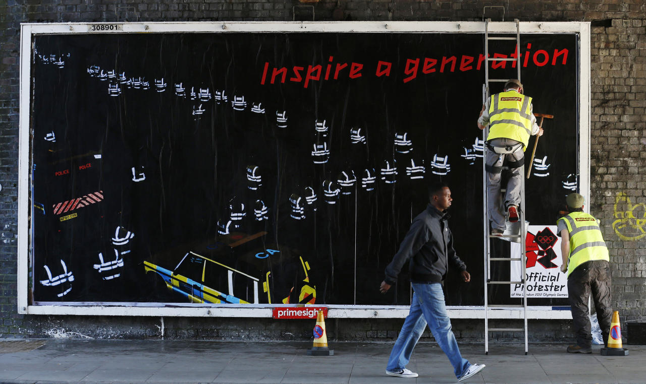 Guerrilla artists put up a billboard protesting the London 2012 Olympics in east London July 23, 2012. REUTERS/Suzanne Plunkett (BRITAIN - Tags: SPORT OLYMPICS SOCIETY)