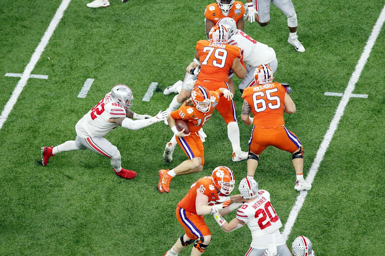 iJan 1, 2021; New Orleans, LA, USA; Clemson Tigers quarterback Trevor Lawrence (16) evades Ohio State Buckeyes defensive tackle Haskell Garrett (92) during the second quarter at Mercedes-Benz Superdome. Mandatory Credit: Russell Costanza-USA TODAY Sports