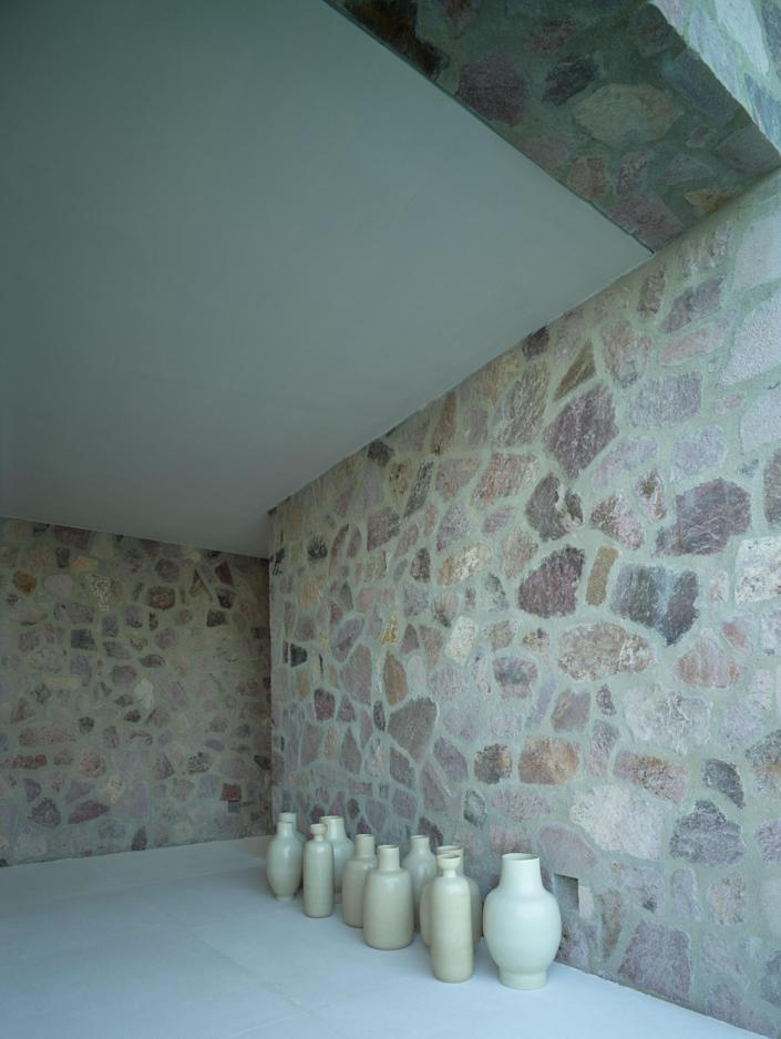 A grouping of Laplace-designed ceramic vases is assembled against a stone wall.