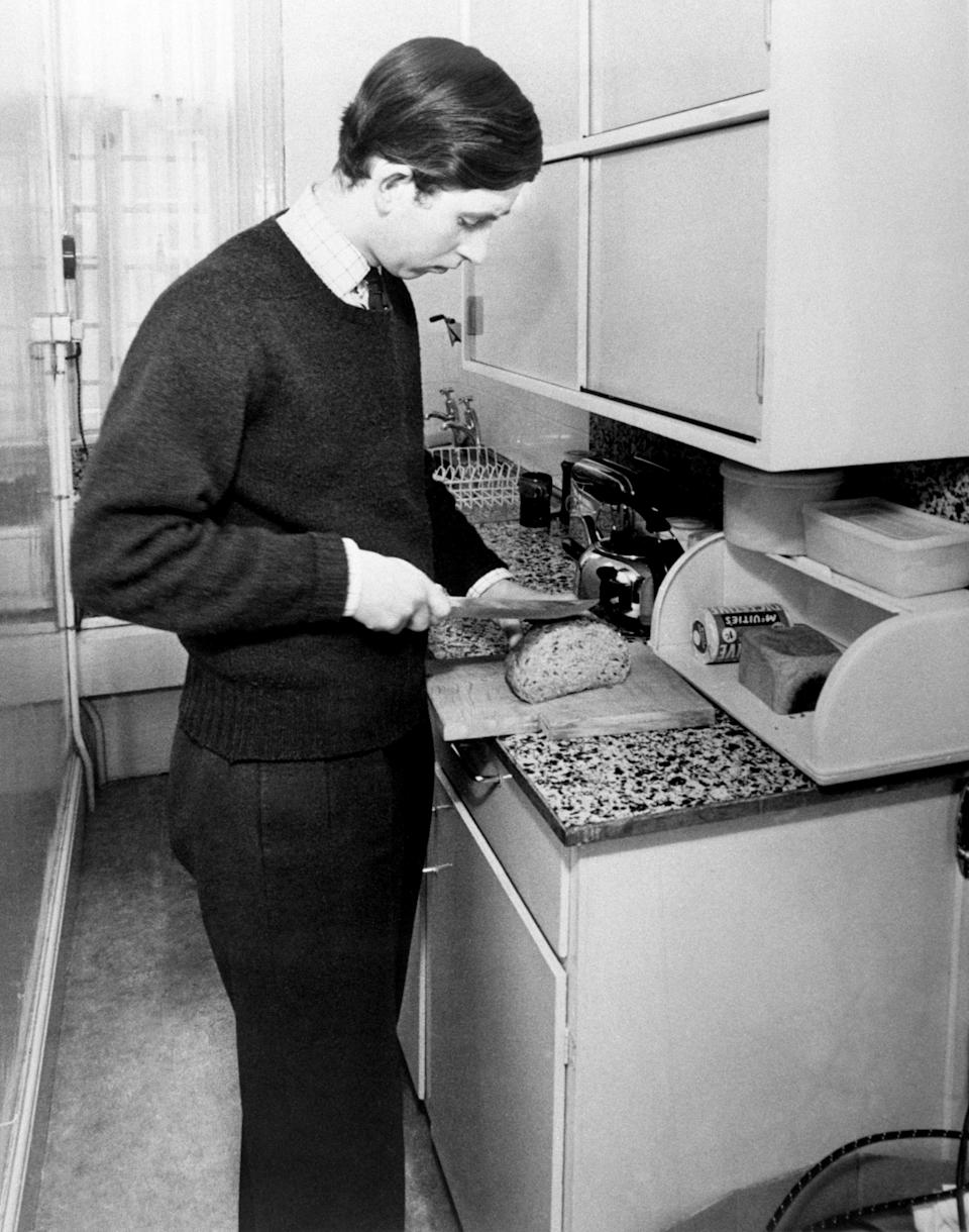 Prince Charles slices a loaf of bread in his student kitchen - perhaps beans on toast is fit for a king-to-be? Photo was taken in May 1969. (PA Images)