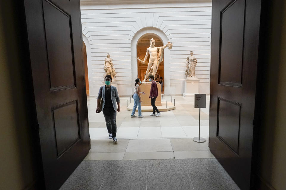 """Visitors to the Metropolitan Museum of Art walk past Antonio Canova's """"Perseus with the Head of Medusa,"""" Thursday, April 29, 2021, in New York. In recent weeks, tourism indicators for New York City like hotel occupancy and museum attendance that had fallen off a pandemic cliff have ticked up slightly. It's a welcome sight for a city where the industry has been decimated by the impact of the coronavirus. (AP Photo/Mary Altaffer)"""