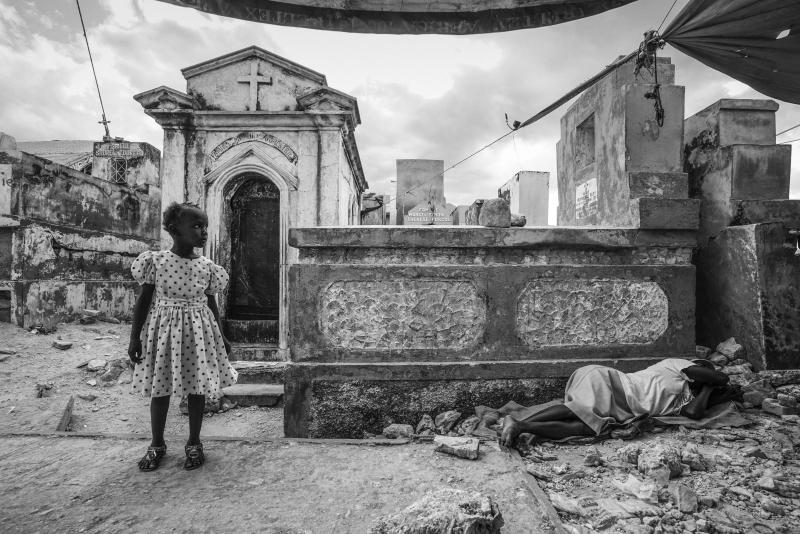On the fifth anniversary of the devastating earthquake, a young child stands to the side of her mourning mother who lies weeping nearby in the Grand Cemetery of Port-Au-Prince, Haiti, Jan. 12, 2015.