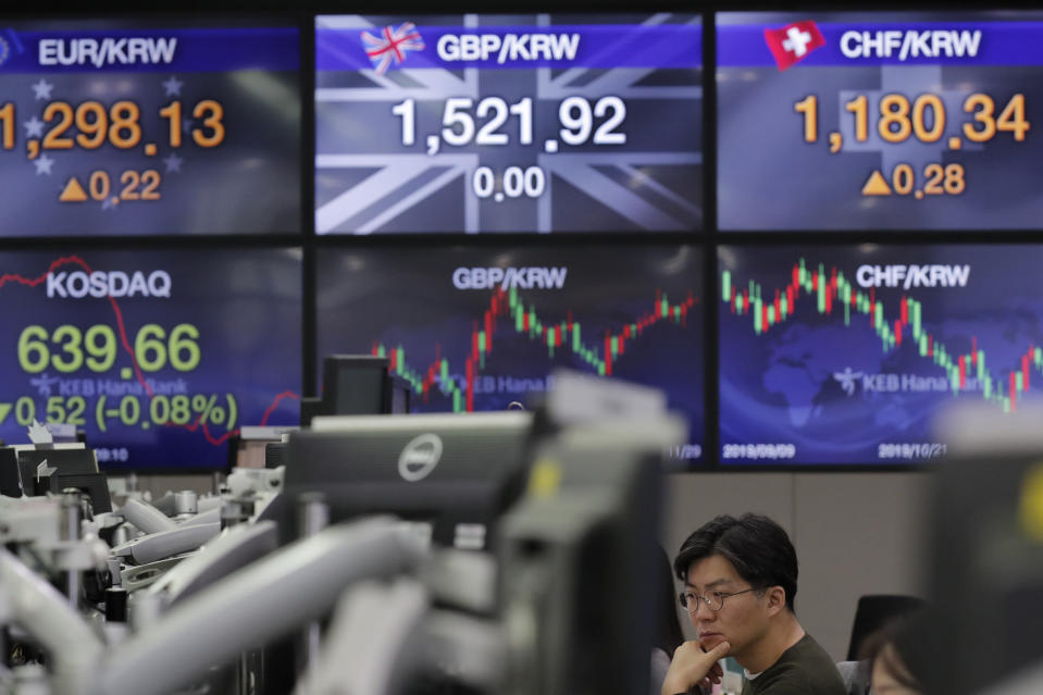 A currency trader watches computer monitors near the screens showing the foreign exchange rates at the foreign exchange dealing room in Seoul, South Korea, Friday, Nov. 29, 2019. Shares extended losses in Asia on Friday after Japan and South Korea reported weak manufacturing data that suggest a worsening toll from trade tensions. (AP Photo/Lee Jin-man)