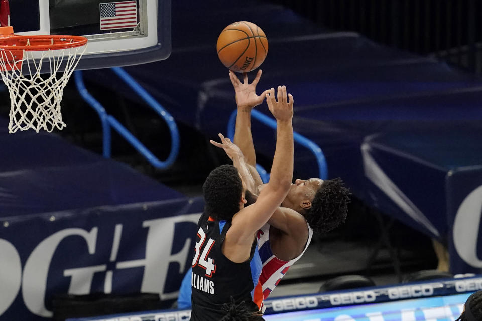 Detroit Pistons guard Saben Lee, right, shoots as Oklahoma City Thunder forward Kenrich Williams (34) defends in the first half of an NBA basketball game Monday, April 5, 2021, in Oklahoma City. (AP Photo/Sue Ogrocki)