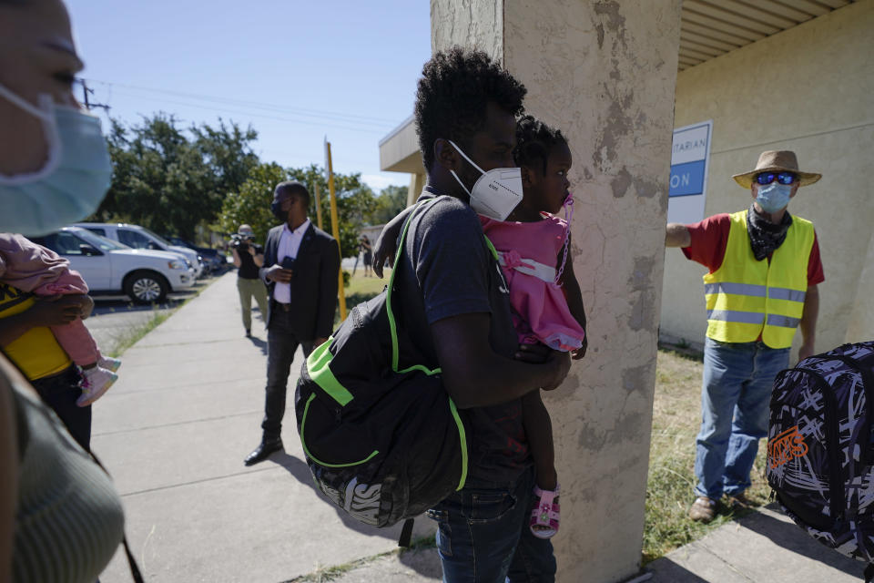 Dave, right, who declined to give his last name, from Toledo, Ohio, wears a neon vest as migrants are released from U.S. Customs and Border Protection custody, Friday, Sept. 24, 2021, in Del Rio, Texas. Dave, who has been to Haiti many times, befriended a woman named Ruth, who he believes is still in custody after she crossed the Rio Grande with her husband and their 3-year-old daughter. Dave drove down from Ohio to Southwest Texas in hopes of picking the family up and driving them to Ohio, where Ruth has family awaiting them. (AP Photo/Julio Cortez)