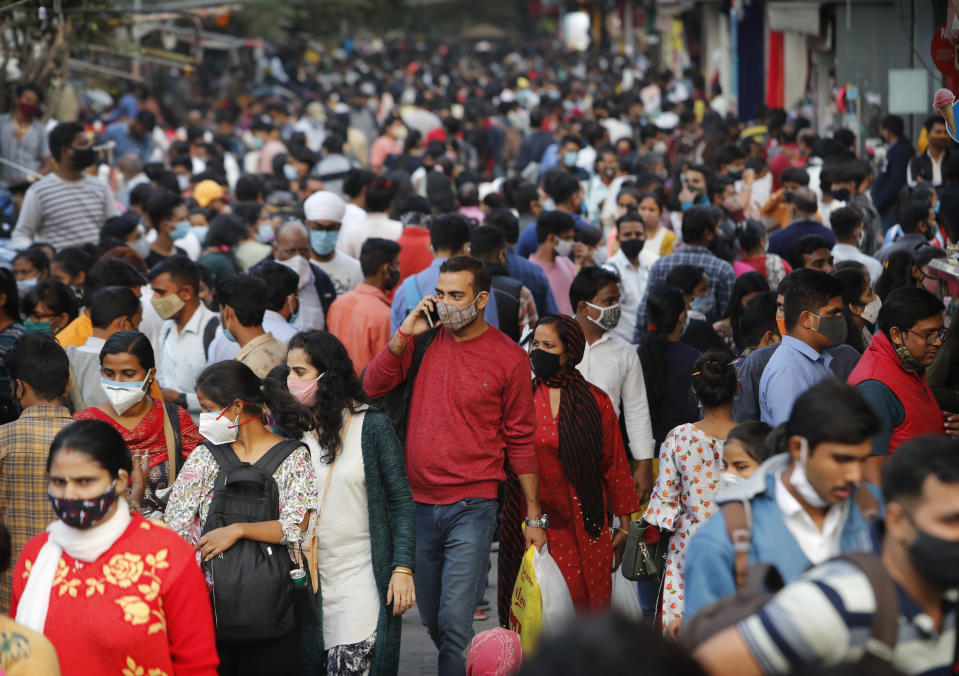 FILE - In this Nov. 12, 2020, file photo, people walk in a market to shop ahead of the Diwalli festival in New Delhi, India. Scientists say it's still too early to predict the future of the coronavirus, but many doubt it will ever go away entirely. (AP Photo/Manish Swarup, File)