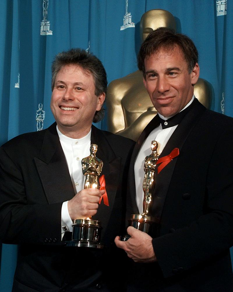 """Alan Menken, left, and Stephen Schwartz smile for photographers backstage after winning for Best Achievement in Music-Original Musical or Comedy Score for """"Pocahontas"""" at the 68th Academy Awards at the Music Center in Los Angeles, Monday, March 25, 1996. (AP Photo/Reed Saxon)"""