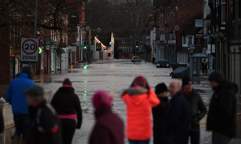People looking at flood water in Tenbury Wells after the River Teme burst its banks in western England.
