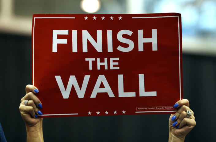 """A supporter of President Donald Trump hold up a sign that reads """"Finish the Wall"""" during a rally at the IX Center, in Cleveland, Monday, Nov. 5, 2018, (AP Photo/Carolyn Kaster)"""