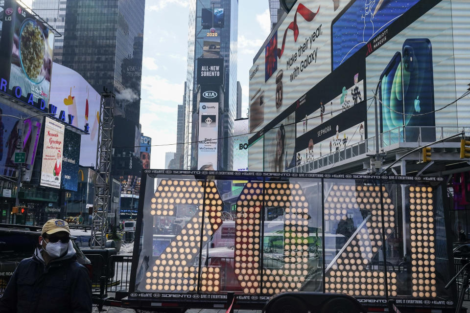 """FILE - In this Dec. 21, 2020, file photo, a man walks past giant numerals for """"2021"""" to be used in the upcoming the New Year's eve festivities in New York's Times Square. (AP Photo/Frank Franklin II, File)"""