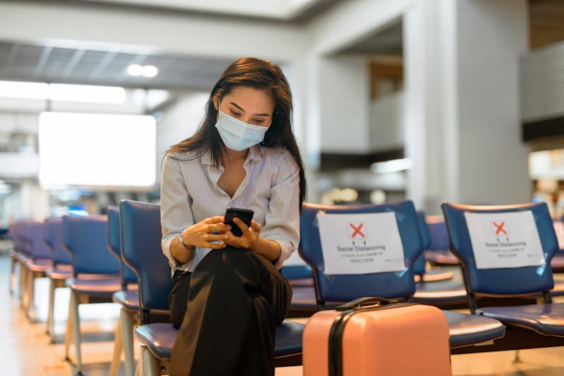 Portrait of young Asian tourist woman with mask for protection from corona virus outbreak social distancing at the airport