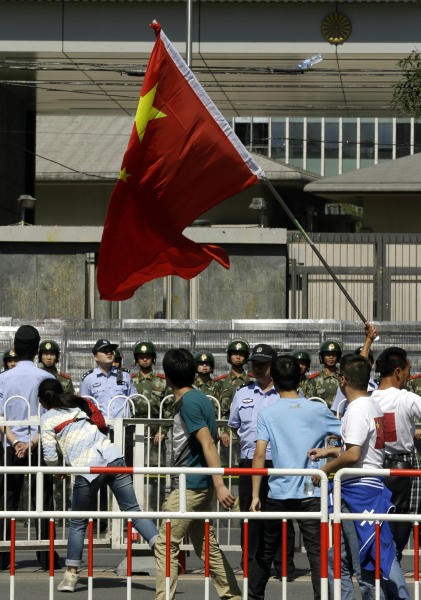 A Chinese protester throws a bottle at the Japanese Embassy in Beijing, China, Monday, Sept. 17, 2012. (AP Photo/Ng Han Guan)