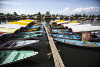 A Kashmiri boatman walks near anchored boats at Srinagar, Indian controlled Kashmir on Aug. 2, 2021. From the Great Wall to the picturesque Kashmir valley, Asia's tourist destinations are looking to domestic visitors to get them through the COVID-19 pandemic's second year. (AP Photo/Mukhtar Khan)