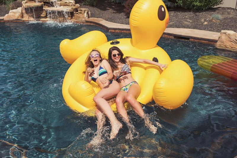Two young women on a inflatable duck in a fancy swimming pool