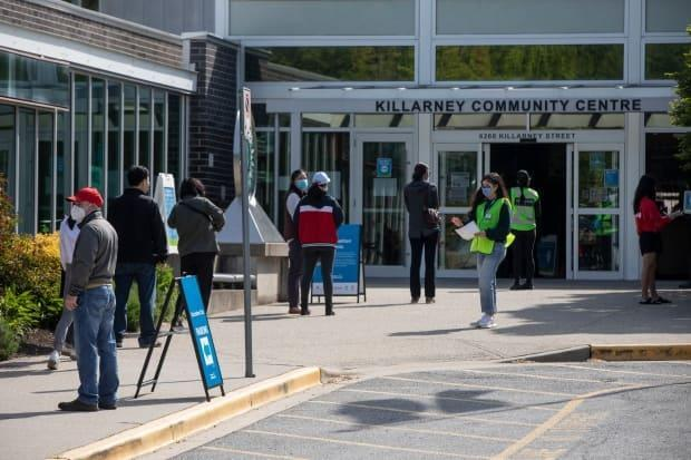People line up outside the Killarney Community Centre to receive their COVID-19 vaccination due to living in a 'hot-spot' neighbourhood in Vancouver, British Columbia on Monday, May 11, 2021. (Ben Nelms/CBC - image credit)