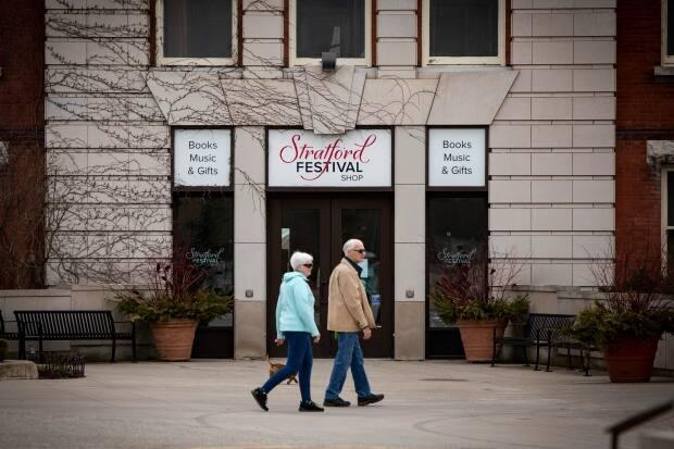The Stratford Festival, which has been holding annual theatre productions in Stratford, Ont., since 1953, will put it's entire 2020 season on hold amidst the COVID-19 pandemic.  See man and woman walking in front of Stratford Festival shop.