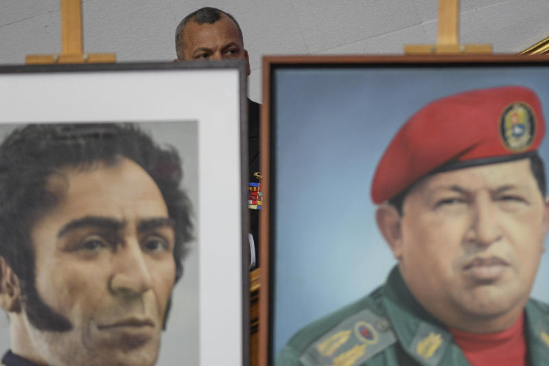 A member of the Venezuelan military sits behind images of late President Hugo Chavez, right, and independence hero Simon Bolivar during the annual address to the nation by Venezuelan President Nicolas Maduro inside the chamber of the Constituent Assembly on the grounds of the National Assembly in Caracas, Venezuela, Tuesday, Jan. 14, 2020. (AP Photo/Matias Delacroix)
