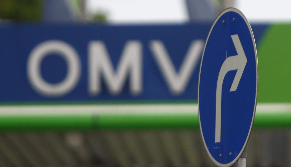 The logo of Austrian oil and gas group OMV is seen at a petrol station behind a road sign in Munich May 8, 2009. OMV reported a worse-than-expected 56 percent fall in clean operation earnings in the fourth quarter as the low oil price hit results. REUTERS/Dominic Ebenbichler (AUSTRIA BUSINESS ENERGY)
