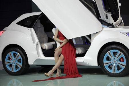 Model sits in a Haval E concept car from China's Great Wall Auto at Auto China 2012 in Beijing