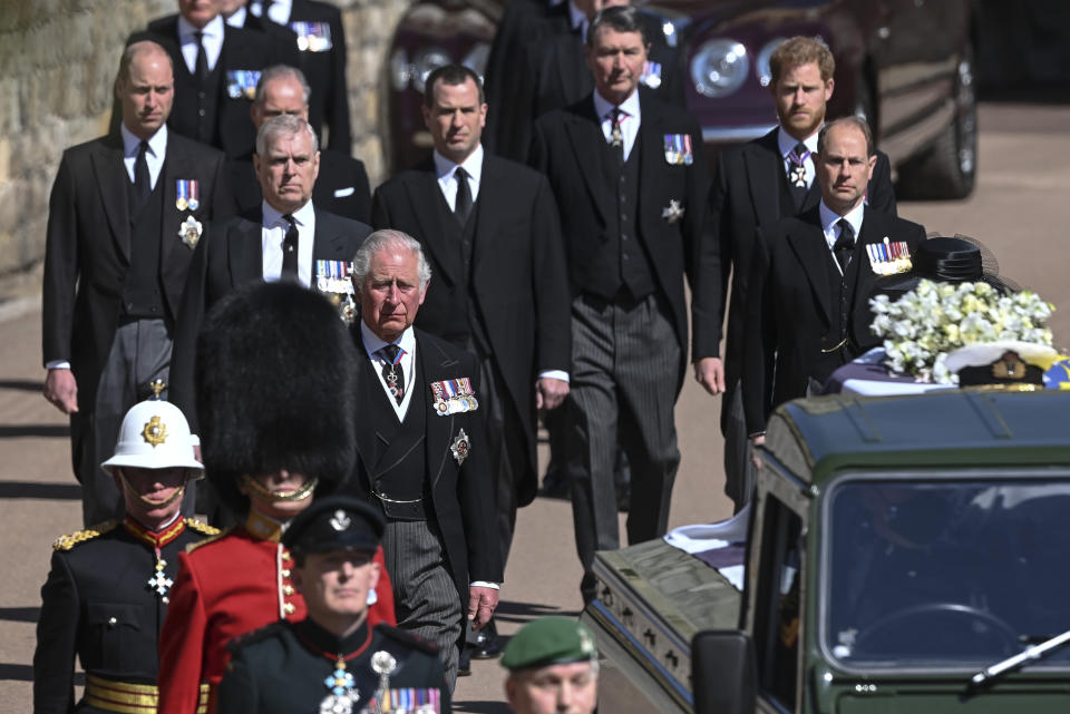 From front left, Britain's Prince Charles, Prince Andrew. Prince Edward, Prince William, Peter Phillips, Prince Harry, Earl of Snowdon and Tim Laurence follow the coffin the coffin makes it's way past the Round Tower during the funeral of Britain's Prince Philip inside Windsor Castle in Windsor, England Saturday April 17, 2021. (Leon Neal/Pool via AP)