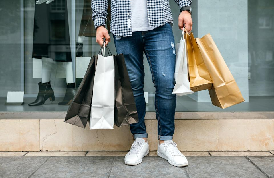 Low Section Of Young Man Holding Shopping Bags While Standing On Sidewalk