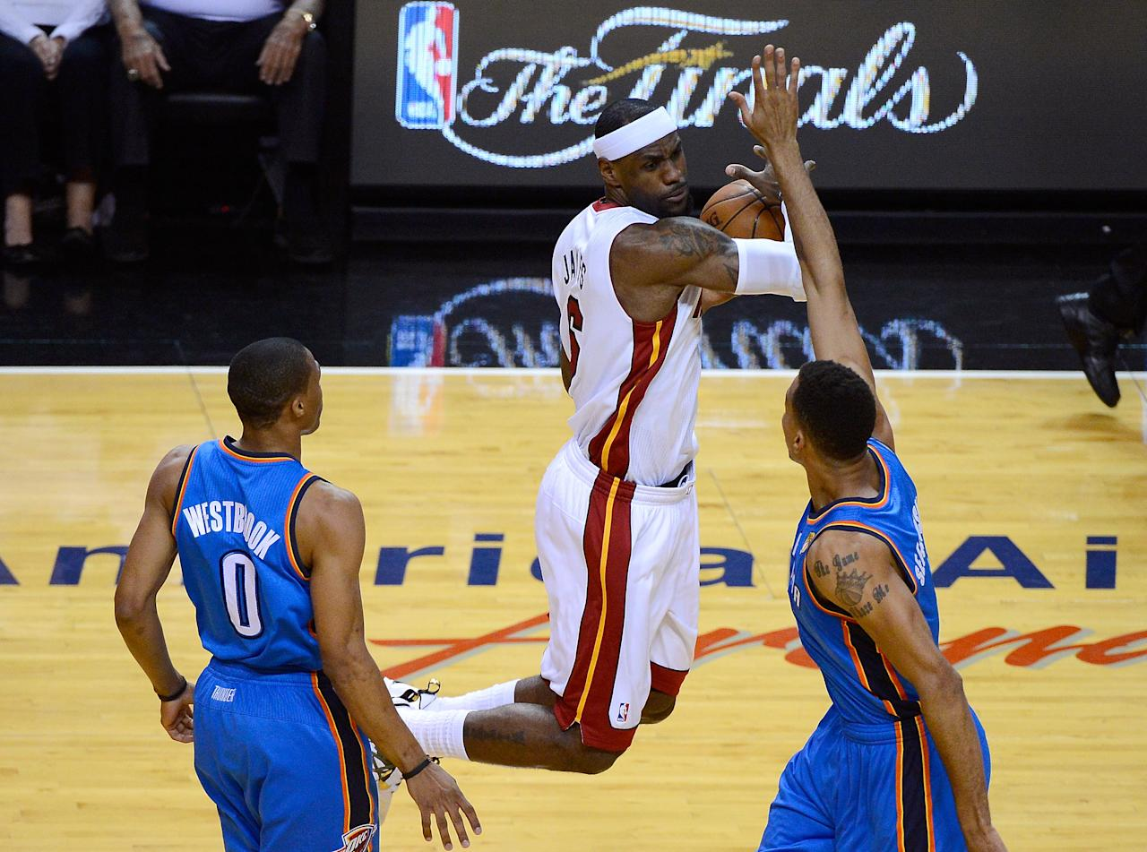 MIAMI, FL - JUNE 17:  LeBron James #6 of the Miami Heat attempts to control the ball in the first quarter against Russell Westbrook #0 and Thabo Sefolosha #2 of the Oklahoma City Thunder in Game Three of the 2012 NBA Finals on June 17, 2012 at American Airlines Arena in Miami, Florida.  NOTE TO USER: User expressly acknowledges and agrees that, by downloading and or using this photograph, User is consenting to the terms and conditions of the Getty Images License Agreement.  (Photo by Ronald Martinez/Getty Images)