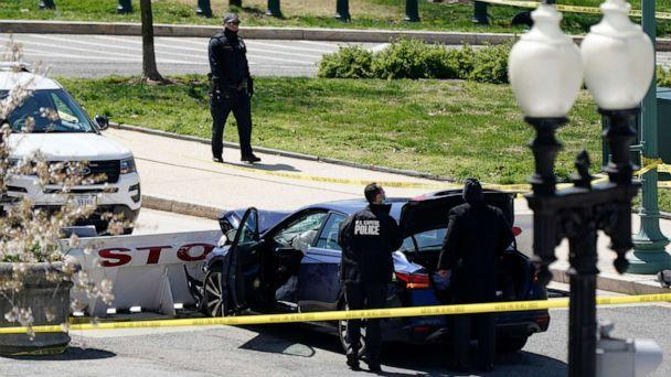 PHOTO: U.S. Capitol Police officers stand near a car that crashed into a barrier on Capitol Hill in Washington on April 2, 2021. (J. Scott Applewhite/AP)