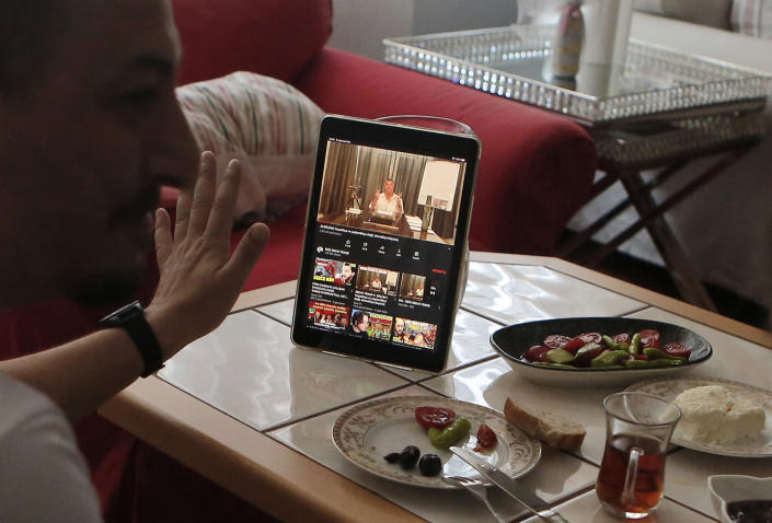 Alparslan Atas, 41, left, gestures as he talks to his wife Gulistan, 38, over breakfast at their home in Istanbul, while watching on a tablet Sedat Peker, a Turkish fugitive crime boss on a video, Sunday, June 6, 2021. Sunday is the day the 49-year-old convicted crime ringleader posts the latest installation of his hour-long tell-all videos from his stated base in Dubai that have captivated Turkey and turned the mobster into an unlikely social media phenomenon. The convicted crime ringleader has been dishing the dirt on members of Turkish President Recep Tayyip Erdogan's ruling party. The allegations range from drug trafficking and a murder cover-up to weapons transfers to Islamic militants. (AP Photo/Mehmet Guzel)
