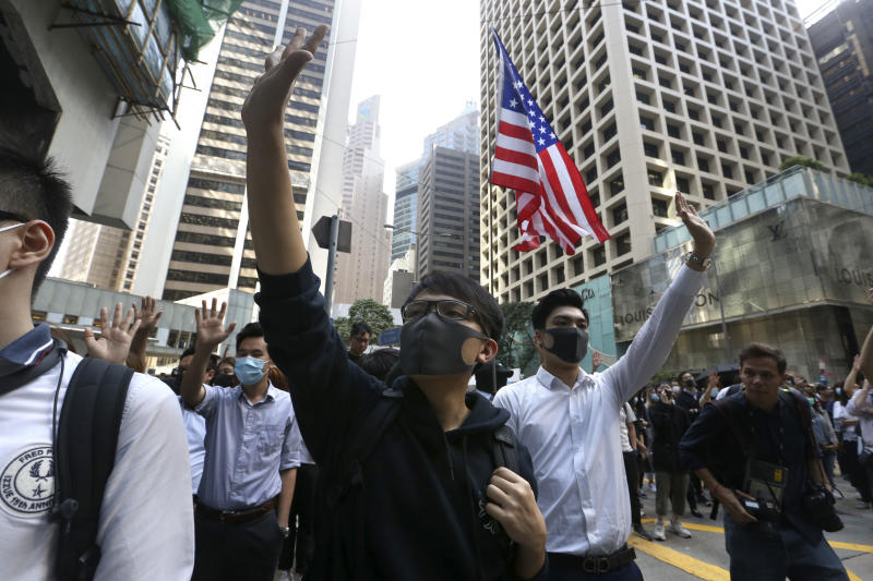 Demonstrators raise their hands during a protest in the financial district in Hong Kong, Friday, Nov. 15, 2019. Protesters who have barricaded themselves in a Hong Kong university partially cleared a road they were blocking and demanded that the government commit to holding local elections on Nov. 24. (AP Photo/Achmad Ibrahim)