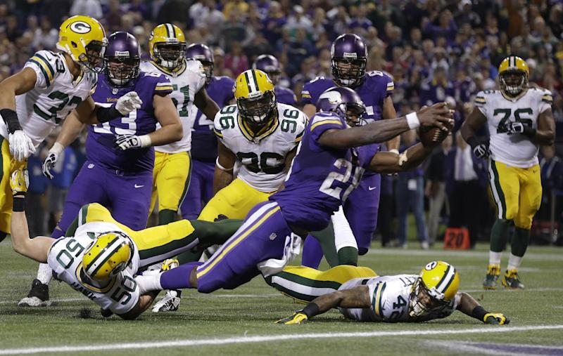 Minnesota Vikings running back Adrian Peterson (28) dives into the end zone for a touchdown in the first half of an NFL football game against the Green Bay Packers, Sunday, Oct. 27, 2013, in Minneapolis. (AP Photo/Jim Mone)