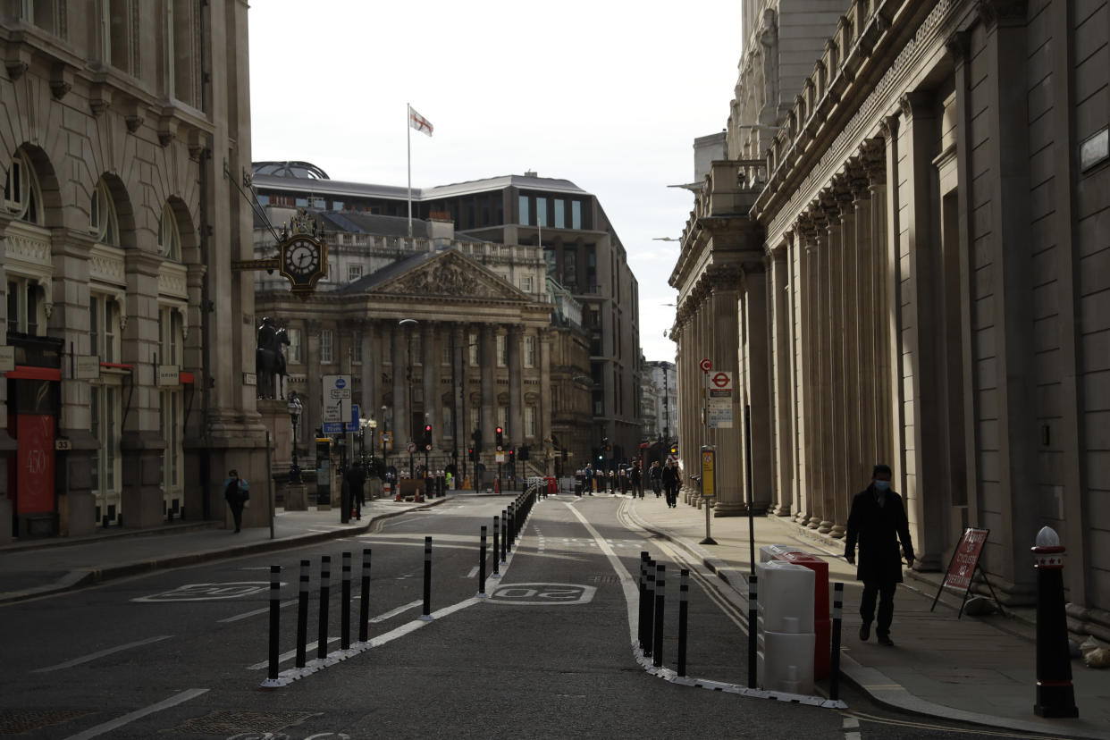 People walk past the Bank of England, at right, in the City of London financial district of London, during England's third coronavirus lockdown, Tuesday, Feb. 23, 2021. British Prime Minister Boris Johnson announced on Monday a slow easing of one of Europe's strictest pandemic lockdowns, with non-essential shops and hairdressers due to reopen April 12. (AP Photo/Matt Dunham)