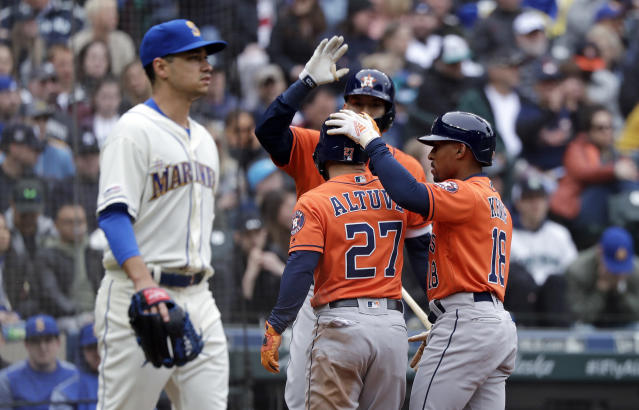 Seattle Mariners starting pitcher Marco Gonzales, left, heads back to the mound as Houston Astros' Jose Altuve (27) and Tony Kemp (18) celebrate scoring with Carlos Correa in the sixth inning of a baseball game Sunday, April 14, 2019, in Seattle. (AP Photo/Elaine Thompson)