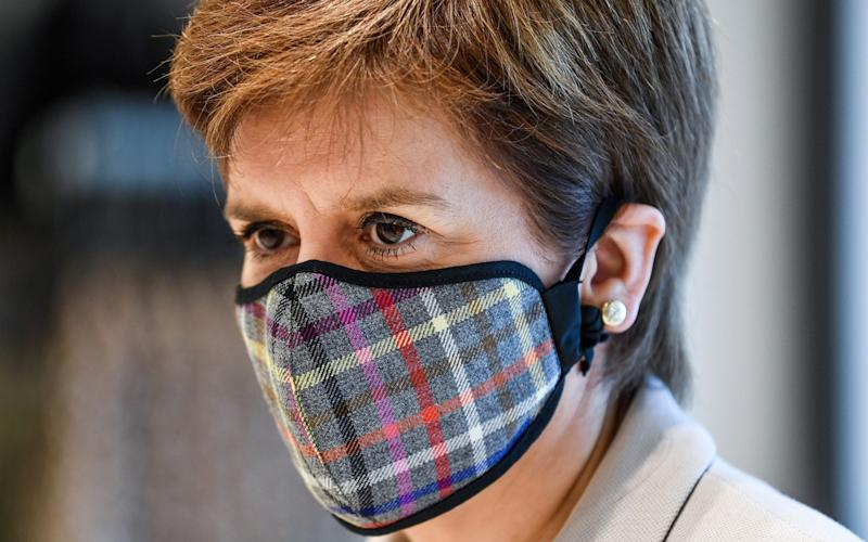 First Minister of Scotland Nicola Sturgeon wears a Tartan mask as she visits New Look at Fort Kinnaird Retail Park, in Edinburgh, Scotland June 26, 2020. - Jeff J Mitchell/Pool via Reuters