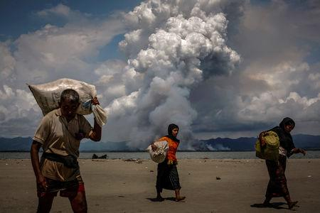 FILE PHOTO: Smoke is seen on the Myanmar border as Rohingya refugees walk on the shore after crossing the Bangladesh-Myanmar border