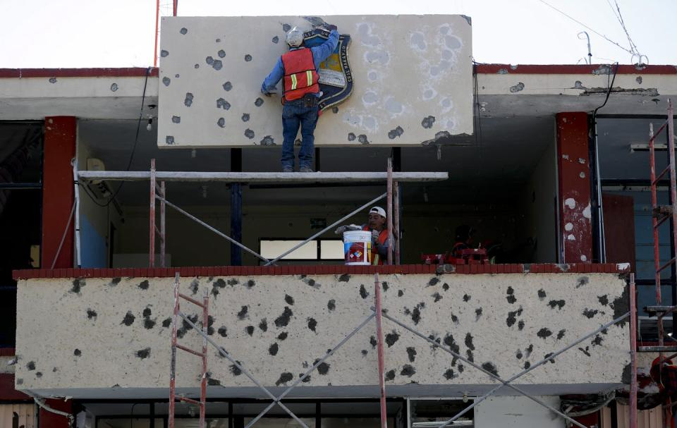 Workers repair the facade of a government building riddled with bullet holes.