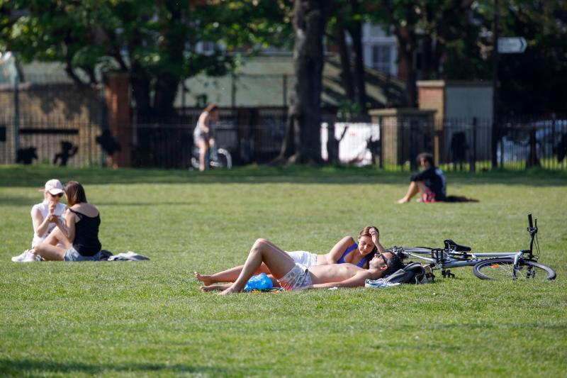 "People sunbathe at London Fields in east London on April 24, 2020, during the national lockdown due to the novel coronavirus COVID-19 pandemic. - British Prime Minister Boris Johnson, who is recovering after contracting the new coronavirus, is ""in very good shape"", Health Secretary Matt Hancock said on Friday. (Photo by Tolga AKMEN / AFP) (Photo by TOLGA AKMEN/AFP via Getty Images)"