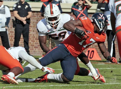 Virginia wide receiver Miles Gooch (17) stretches ahead for a touchdown as Miami linebacker Jimmy Gaines (59) tries to make the stop during the first half of an NCAA college football game in Charlottesville, Va., Saturday, Nov. 10, 2012.. (AP Photo/Steve Helber)