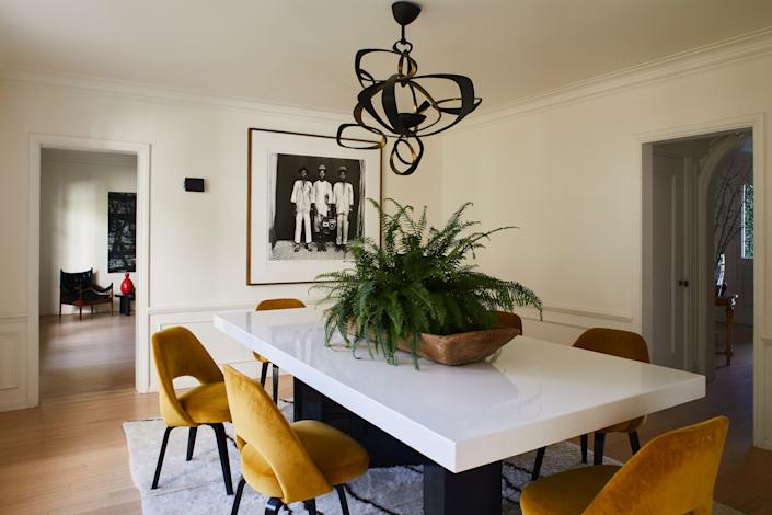 "<div class=""caption""> Dahan brought the Herve Van der Straeten white lacquered table and chandelier from her last home, and reupholstered Eero Saarinen chairs in a sunny shade. A Malick Sidibé photograph (""I'm so happy I have that piece,"" she says) watches over. </div>"