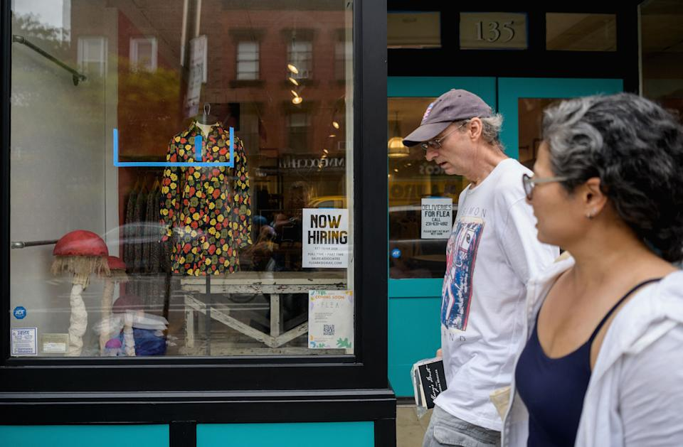 A couple walks past a 'now hiring' sign posted at a store in New York City on August 20, 2021. - US states that ended pandemic jobless benefits early saw slight dips in unemployment rates but big declines in spending and income, according to a study released Friday, in what could be a preview of the effects nationwide when the programs end completely. (Photo by Angela Weiss / AFP) (Photo by ANGELA WEISS/AFP via Getty Images)