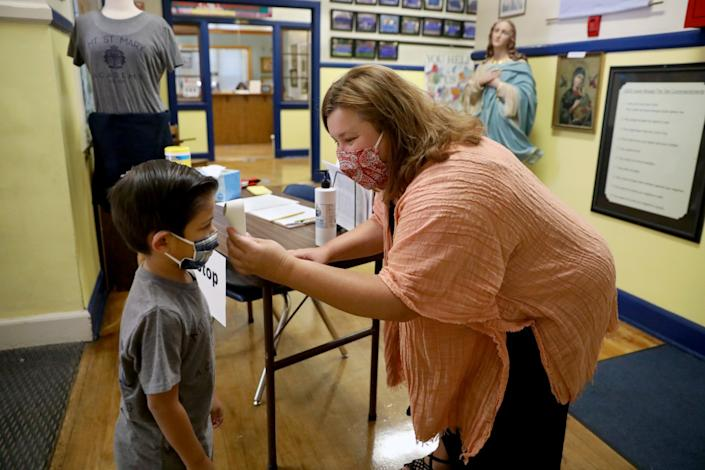"Miles Sirisute, 6, a kindergartner at Mount St. Mary's, has his temperature checked by Principal Edee Wood. <span class=""copyright"">(Gary Coronado / Los Angeles Times)</span>"