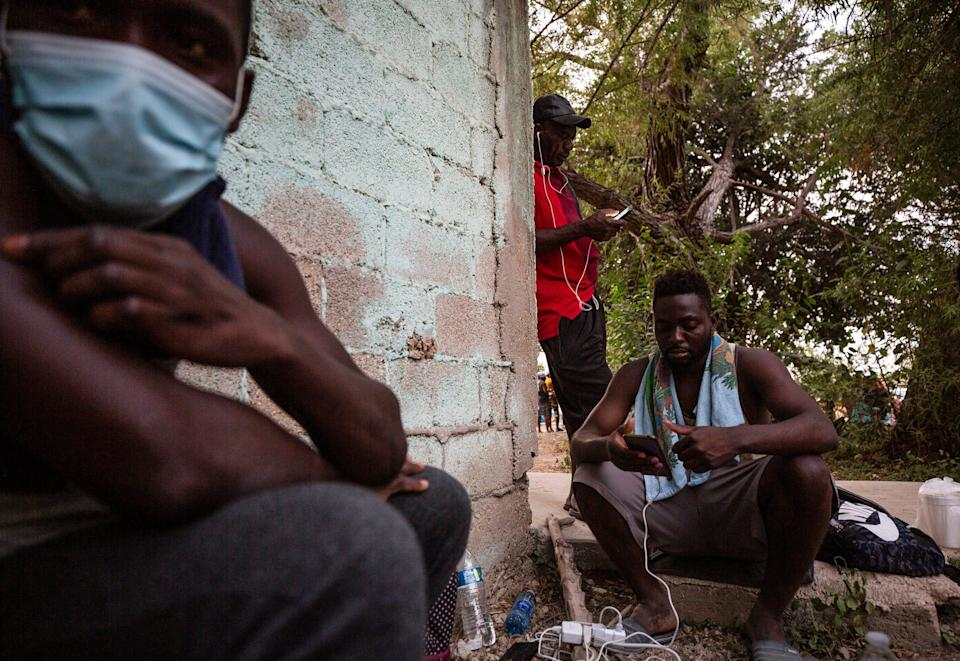 Haitian migrants speak to their loved ones after charging their phones at the Braulio Fernandez park in Ciudad Acuna on Tuesday Sept. 21, 2021.