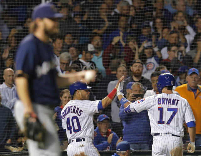 Chicago Cubs' Willson Contreras, center, celebrates scoring a run with Chicago Cubs' Kris Bryant, right, against Milwaukee Brewers' Wade Miley during the fifth inning of a baseball game Monday, Sept. 10, 2018, in Chicago. (AP Photo/Jim Young)