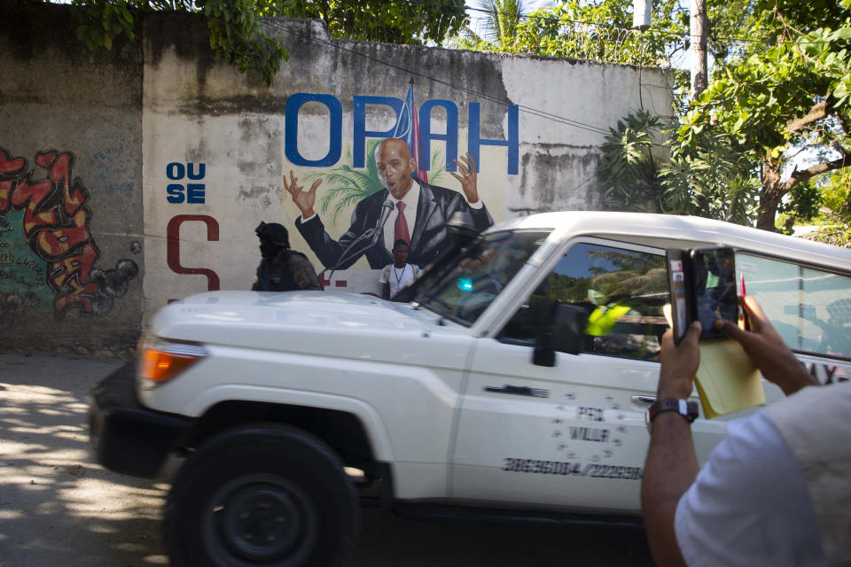 An ambulance carrying the body of Haiti's President Jovenel Moise drives past a mural featuring him near the leader's residence where he was killed by gunmen in the early morning in Port-au-Prince, Haiti, Wednesday, July 7, 2021. Claude Joseph, the interim prime minister, confirmed the killing and said the police and military were in control of security in Haiti. (AP Photo/Joseph Odelyn)