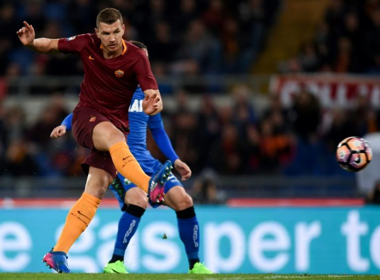 Roma's forward Edin Dzeko (L) shoots and scores against Sassuolo at the Olympic Stadium in Rome on March 19, 2017