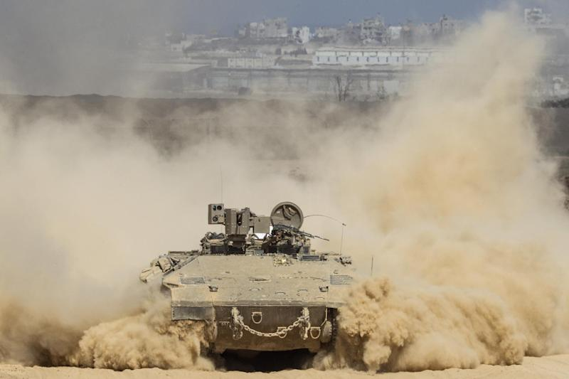 An Israeli army armoured personnel carrier (APC) moves along Israel's border with the Hamas-controlled Gaza Strip on July 25, 2014