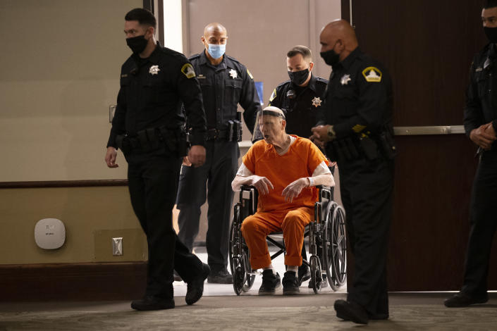 Sacramento County Sheriff's Deputies use a wheelchair to bring Joseph James DeAngelo into the courtroom in Sacramento Superior Court in Sacramento, Calif. Monday, June 29, 2020. DeAngelo, 74, pleaded guilty to 13 counts of murder and multiple other charges 40 years after a sadistic series of assaults and slayings in California. Due to the large numbers of people attending, the hearing was held at a ballroom at California State University, Sacramento to allow for social distancing. (AP Photo/Rich Pedroncelli)