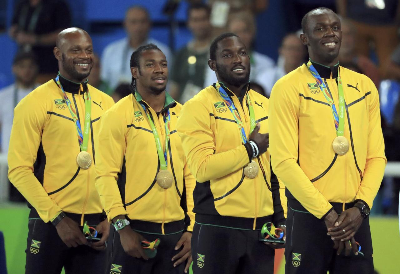 2016 Rio Olympics - Athletics - Victory Ceremony - Men's 4 x 100m Relay Victory Ceremony - Olympic Stadium - Rio de Janeiro, Brazil - 20/08/2016. Gold winners Asafa Powell (JAM), Yohan Blake (JAM), Nickel Ashmeade (JAM) and Usain Bolt (JAM) of Jamaica react on the podium. REUTERS/Dominic Ebenbichler FOR EDITORIAL USE ONLY. NOT FOR SALE FOR MARKETING OR ADVERTISING CAMPAIGNS.