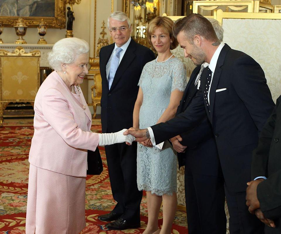 <p>Mr. Beckham first met the Queen in 2003 when he received an OBE. More than a decade later, in 2015, the soccer star joined her Majesty at Buckingham Palace for a reception of the Queen's Young Leaders program and opted for a black-and-white polka dot tie.</p>